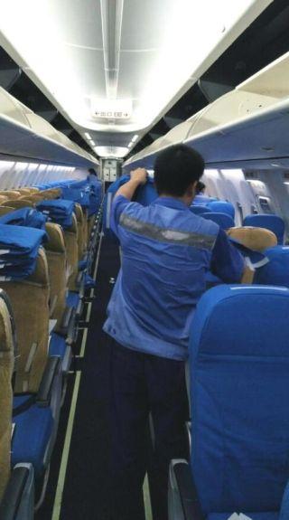 客舱保障员们在温度高达五十余度的闷热客舱中更换全机椅套,汗水早已浸湿她们的工作服。(李伟丽 摄)