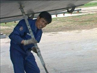 机务人员王育林在检修维护、固定运五飞机。