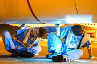 """发动机底部,做完维护工作的两名工作人员将发动机包皮盖好扣紧,""""猫着腰""""做着最后的复查。 (摄影:张立维)"""
