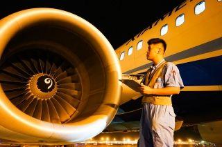 机务工作人员对照着工卡,逐项检查飞机。 (摄影:张立维)
