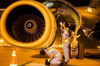 """两名机务""""蓝精灵""""正一丝不苟地检查飞机发动机。 (摄影:张立维)"""