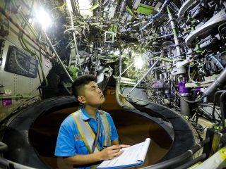 """轮舱内,管路与设备位置错综复杂,但难不倒厦航机务""""蓝精灵""""。 (摄影:张立维)"""