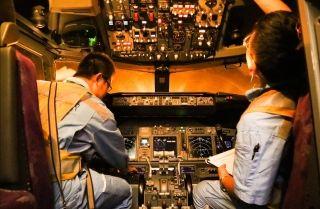 """机务""""蓝精灵""""正在驾驶舱做各种调试检查工作。 (摄影:张立维)"""