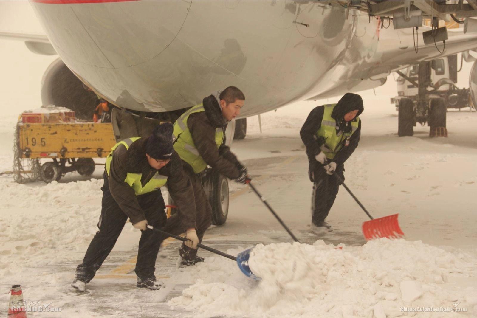 """图:12月1日乌鲁木齐机场遭遇""""沙尘雪""""机务紧张的进行除冰雪工作 供图/乌鲁木齐机场"""