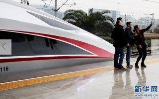 """1月5日,几名旅客在上海虹桥站站台上与G16次""""复兴号""""高铁列车合影。  新华社记者 方喆 摄"""