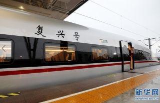 """1月5日,在上海虹桥站,G16次""""复兴号""""高铁列车开车前,乘务员在17号车车门处检视站台。 新华社记者 方喆 摄"""