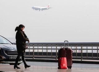 旅客带着大包小包搭乘飞往各地的航班。 (摄影:陶冉)