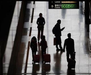 家长领着孩子、拖着登机箱,前往登机口。 (摄影:陶冉)