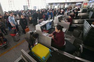 前往柜台办理托运手续的旅客排起了长队。 (摄影:陶冉)