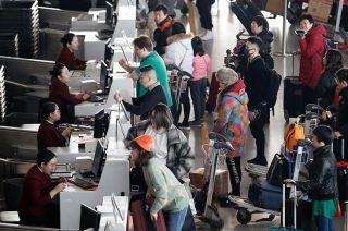 值机柜台办理登机牌和托运行李的旅客。 (摄影:陶冉)