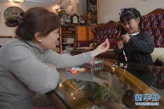 """谈及女儿,刘黎满眼都是温柔:""""她挺懂事的,平时都是爷爷奶奶带着在杨家坪住,我们只能休息日回去陪陪她。""""练黎笑道:""""我们都说她是'城市留守儿童'。"""" 新华网 李相博 摄"""