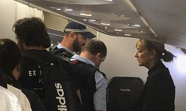 警方登机将女乘客带走 图片来源:《每日邮报》