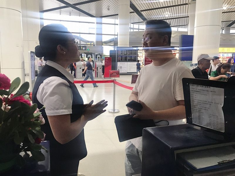 旅客领取遗失的手包并对海航地服工作人员表示感谢