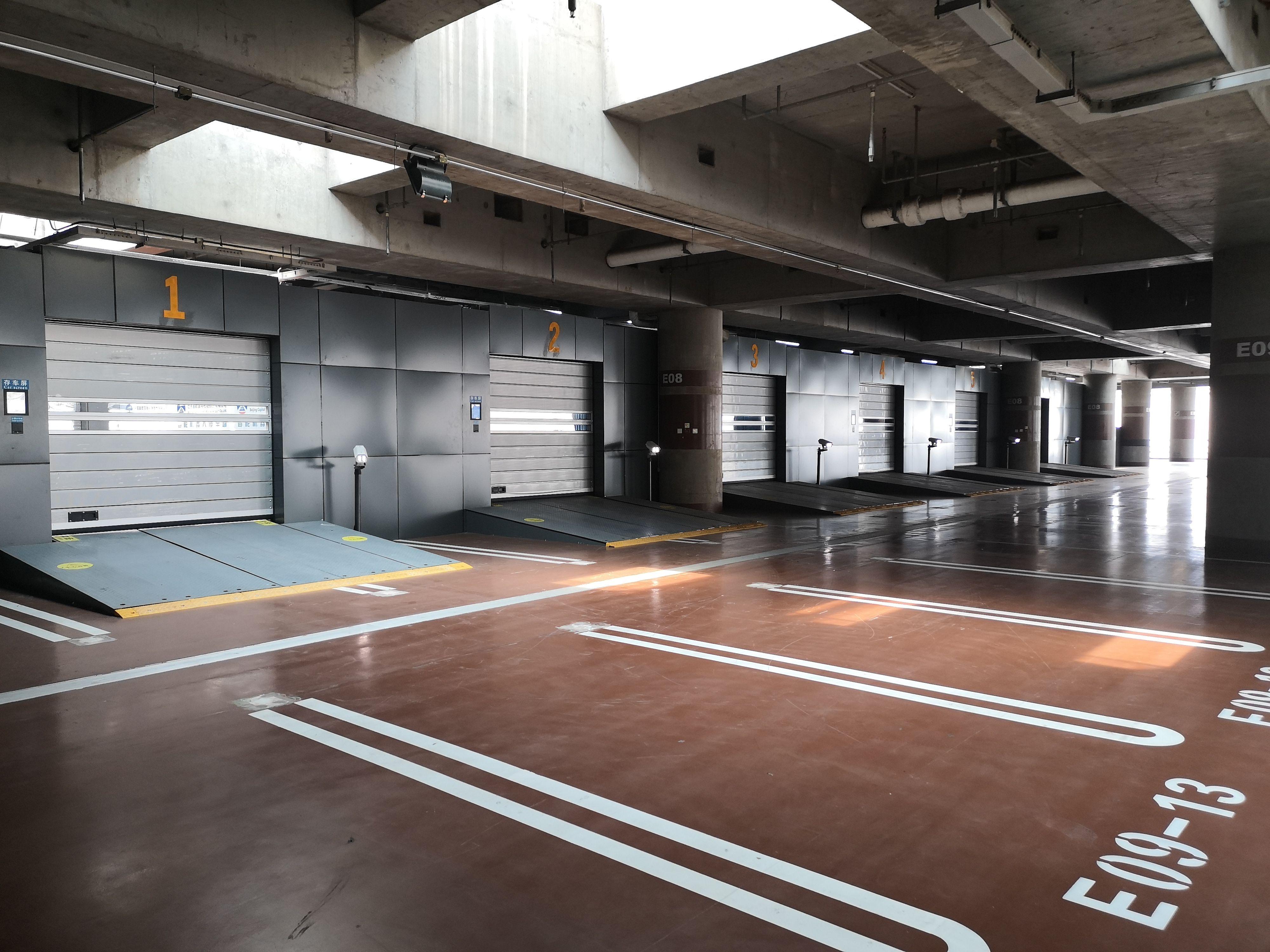 旅客将车辆存入泊车房,停车机器人就能完成升举、搬运、旋转、入库等动作,将车辆送到车位。摄影/新京报记者