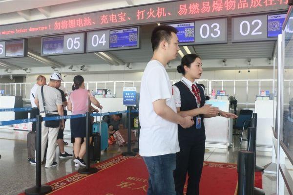 """工作人员向旅客介绍""""无纸化""""乘机流程 摄影:石明慧"""