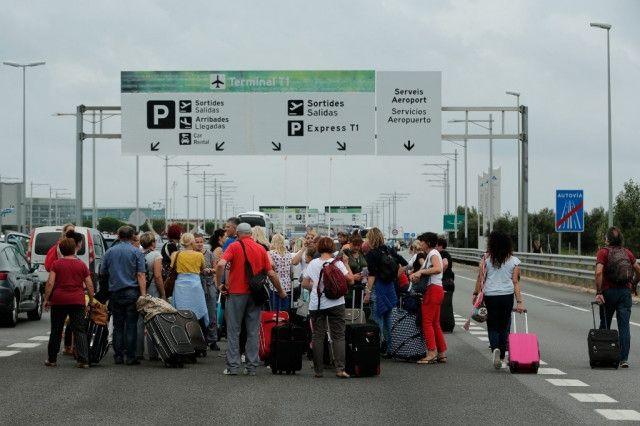 旅客拉着行李箱走在巴塞罗机场高速路上