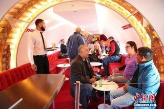 """当地时间11月30日,纽约肯尼迪机场TWA机场酒店将一架老式""""星座""""客机改建为鸡尾酒吧,机舱内的酒吧顾客满座。中新社记者 廖攀 摄"""