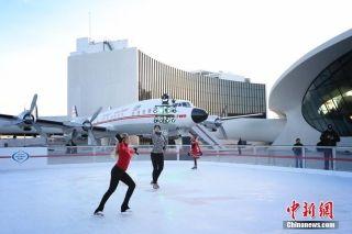 """当地时间11月30日,纽约肯尼迪机场TWA机场酒店新建滑冰场营业第一天受到民众欢迎,许多民众前来老式""""星座""""客机前滑冰。中新社记者 廖攀 摄"""