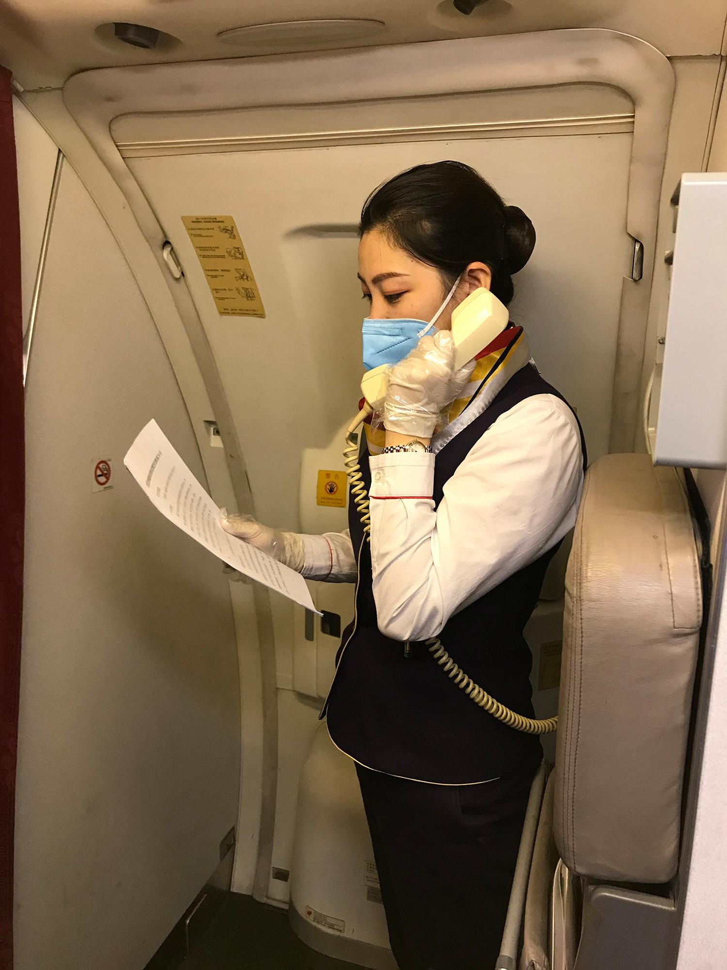 北部湾航空乘务教员管绚通过机上广播为旅客介绍疫情防控法规