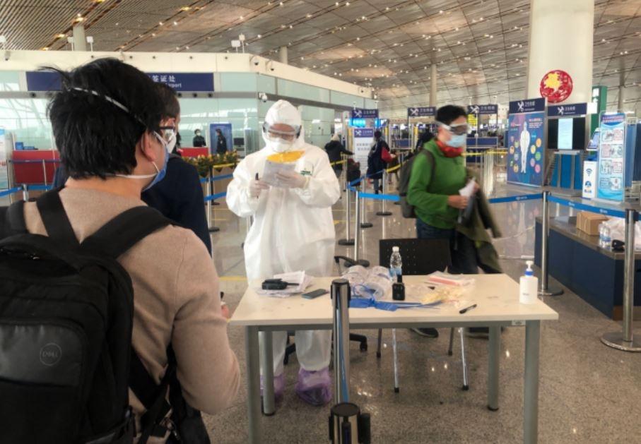 8日,首都机场T3航站楼入境大厅,乘客正在交健康申明卡。