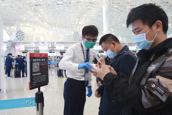 深航工作人员帮助旅客填写健康申报二维码。 摄影:郑毅