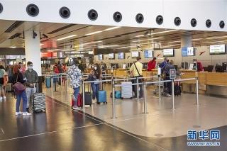 6月15日,在奥地利维也纳国际机场,旅客们在柜台值机。 新华社发(乔治斯·施耐德 摄)