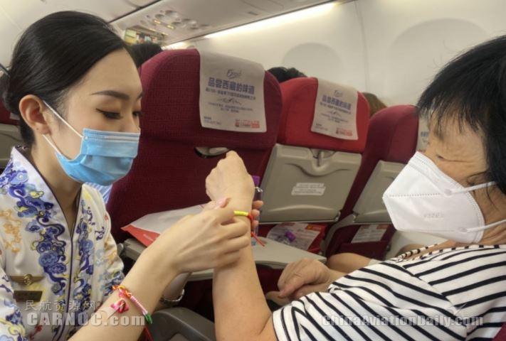 海南航空端午节主题航班乘务员为旅客系饱含祈福纳吉美好寓意的五彩绳