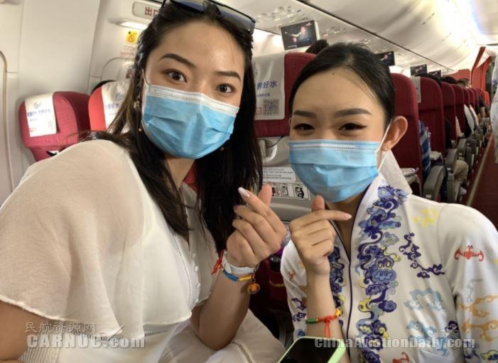 海南航空端午节主题航班乘务员与旅客在航班内共系五彩绳比心合影