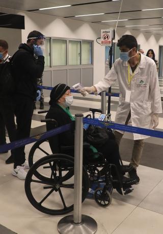 7月1日,在位于黎巴嫩首都贝鲁特的拉菲克·哈里里国际机场,工作人员为抵达旅客测量体温。新华社发(比拉尔•贾维希摄)
