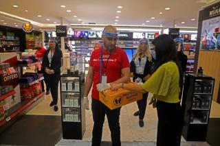 7月1日,在位于黎巴嫩首都贝鲁特的拉菲克·哈里里国际机场,工作人员向旅客提供一次性手套。新华社发(比拉尔•贾维希摄)