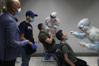 7月1日,在位于黎巴嫩首都贝鲁特的拉菲克·哈里里国际机场,工作人员为抵达旅客进行新冠病毒检测采样。新华社发(比拉尔•贾维希摄)