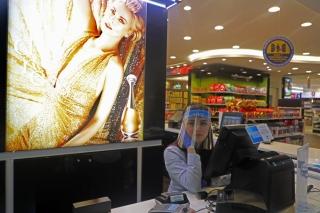 7月1日,在位于黎巴嫩首都贝鲁特的拉菲克·哈里里国际机场,一家免税店员工佩戴防护性面罩工作。新华社发(比拉尔•贾维希摄)