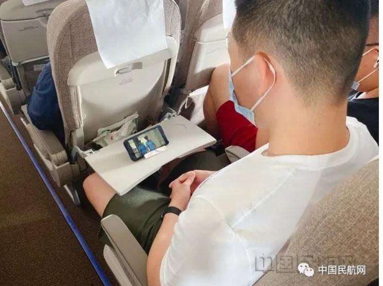 旅客用支架来手机追剧。东航客舱供图