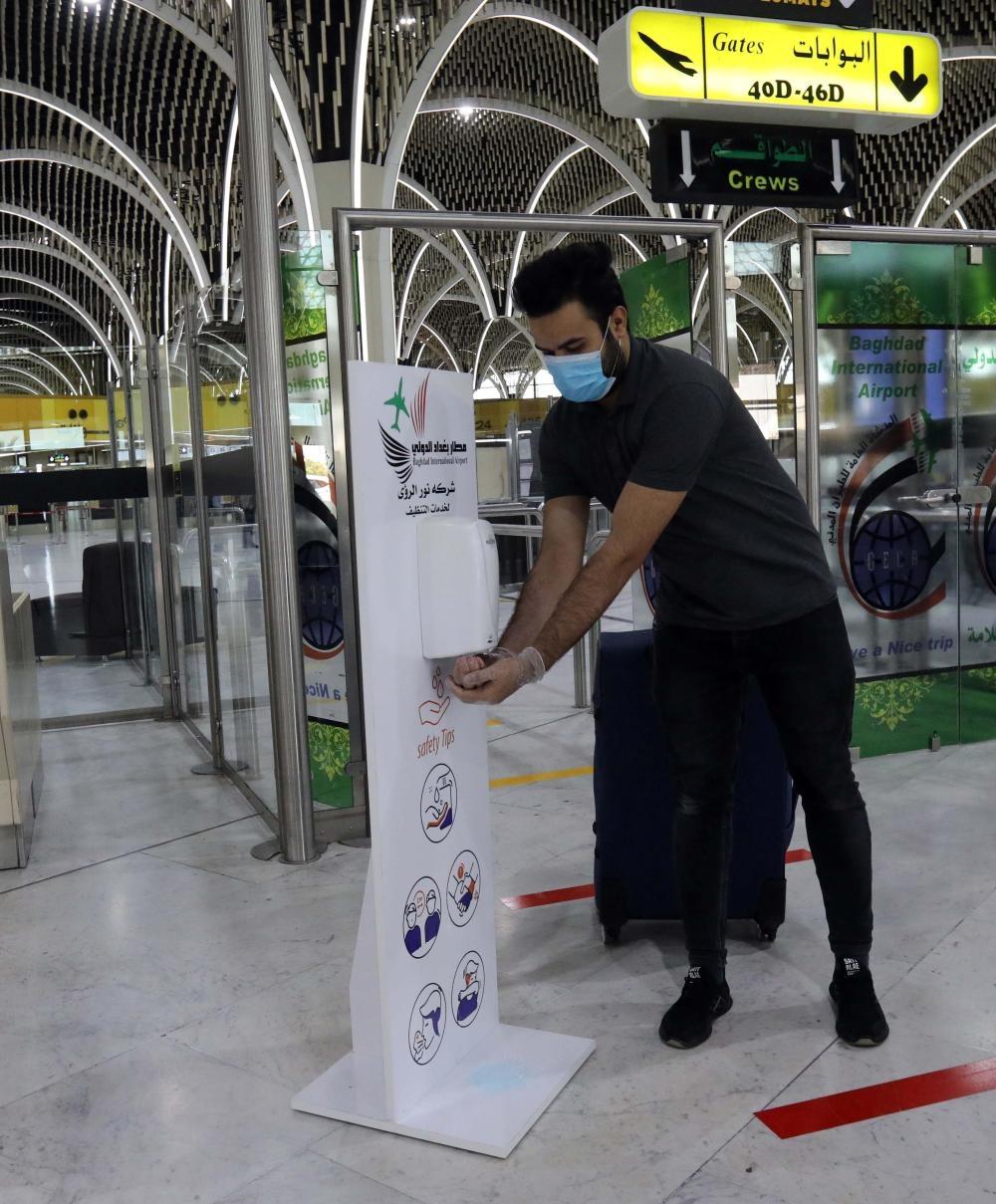 7月23日,在伊拉克巴格达国际机场,一名乘客洗手消毒。
