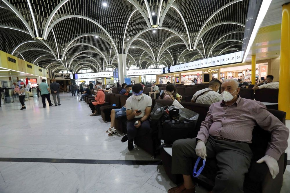 7月23日,在伊拉克巴格达国际机场,乘客戴着口罩在候机大厅等待登机。