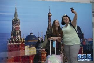 8月1日,在俄罗斯首都莫斯科的谢列梅捷沃机场,乘客在拍照。新华社发(亚历山大摄)