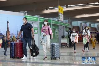 8月1日,在俄罗斯首都莫斯科的谢列梅捷沃机场,乘客戴口罩前行。 新华社发(亚历山大摄)