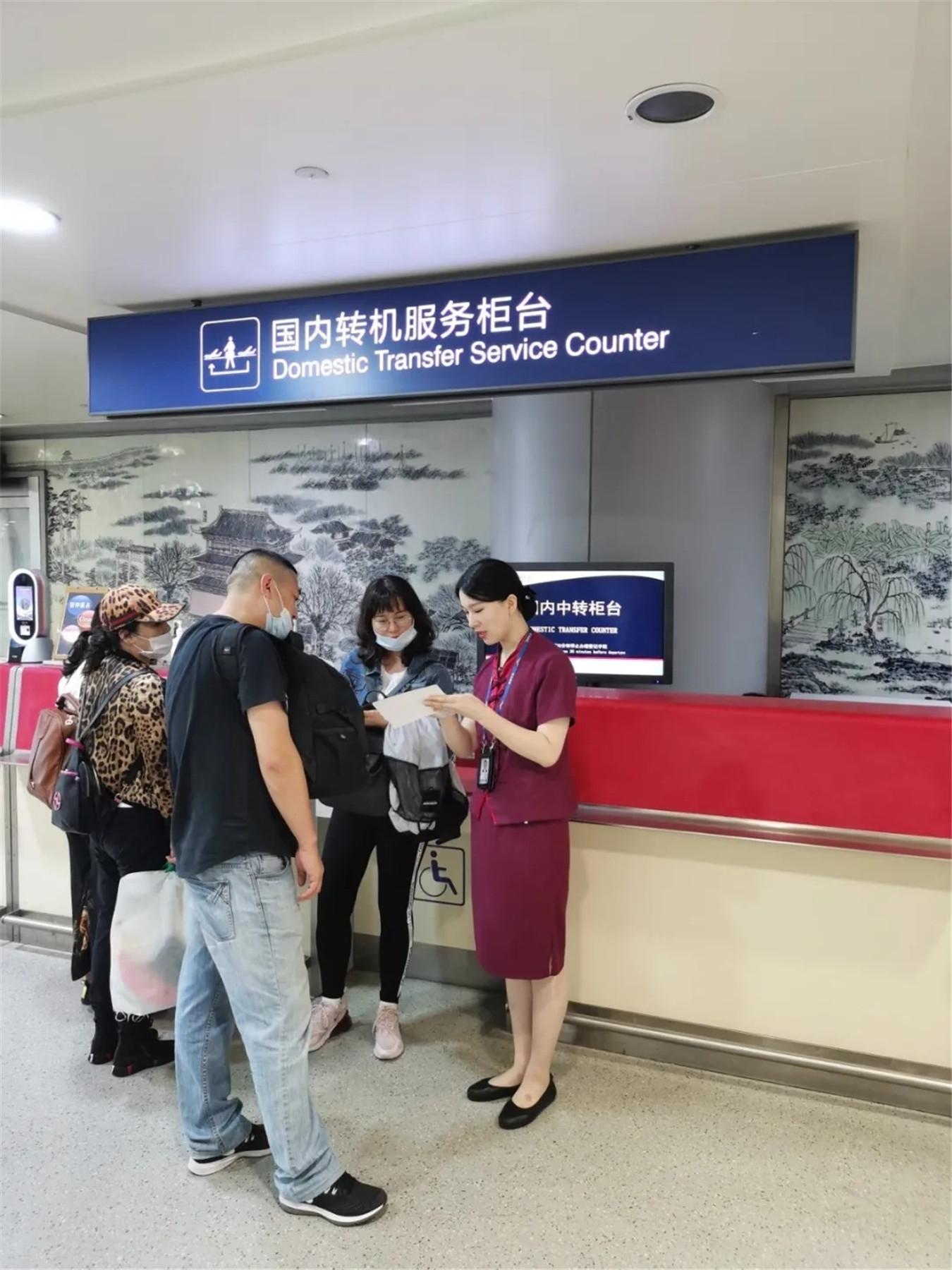 机场工作人员为中转旅客办理手续