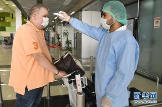 10月1日,工作人员在叙利亚首都大马士革国际机场入口处为乘客测量体温。 因新冠疫情关闭数月后,叙利亚首都大马士革国际机场当日恢复商业航班运营。 新华社发(阿马尔·萨法尔贾拉尼摄)
