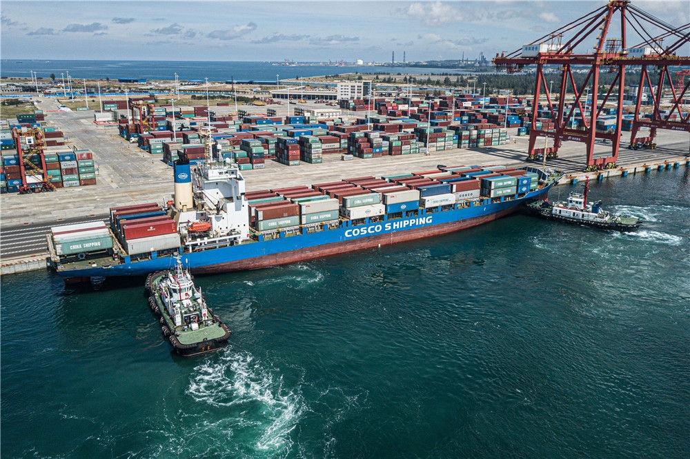 一艘中远海运集装箱货轮在两艘拖轮的辅助下,靠泊进海南洋浦小铲滩码头(9月23日摄,无人机照片)。新华社记者