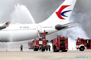 Firefighters react during a mock plane fire as part of an emergency drill held at Pudong International Airport in east China's Shanghai, Oct. 16, 2020. (Xinhua/Chen Fei)