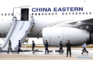 Police officers and dogs enter a passenger plane to search and remove mock explosives as part of an emergency drill held at Pudong International Airport in east China's Shanghai, Oct. 16, 2020. (Xinhua/Chen Fei)