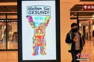 """当地时间10月30日,一块显示屏上的""""柏林熊""""提示人们佩戴口罩。曾有德国""""延宕最久项目""""和""""最大烂尾工程""""之称的柏林新机场(柏林-勃兰登堡维利·勃兰特机场),在启用时间多次推迟达九年后,将于10月31日正式启用。 中新社记者 彭大伟 摄"""