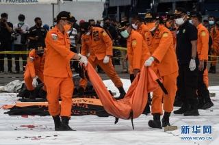 1月10日,搜救人员在印度尼西亚雅加达戈戎不碌港搬运打捞起的失事客机遇难者遗体。新华社发(阿贡摄)