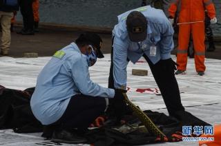 1月10日,搜救人员在印度尼西亚雅加达戈戎不碌港检查打捞起的失事客机残骸。新华社发(阿贡摄)
