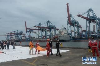 1月10日,搜救人员在印度尼西亚雅加达戈戎不碌港搬运打捞起的失事客机遇难者遗体。 新华社发(阿贡摄)