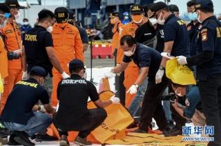 1月10日,搜救人员在印度尼西亚雅加达戈戎不碌港检查打捞起的失事客机遇难者遗体。新华社发(阿贡摄)