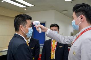 在前往机场执行航班任务前,机组成员们根据疫情防控工作要求,互相协助进行体温检测(摄影:宁隆宇)