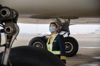7点整,在HU7181航班机组进场后,机长栾贺来到机坪,对飞机进行起飞前的绕机检查(摄影:宁隆宇)