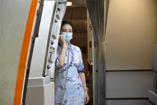乘务长通过客舱广播与组员们沟通,做好迎接旅客登机的准备(摄影:宁隆宇)